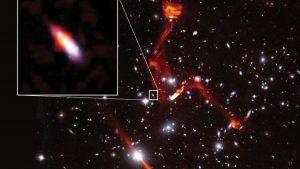 Gökbilimciler, uzaktaki radyo galaksisini incelemek için dev galaksi kümelerini mercek olarak kullanıyor